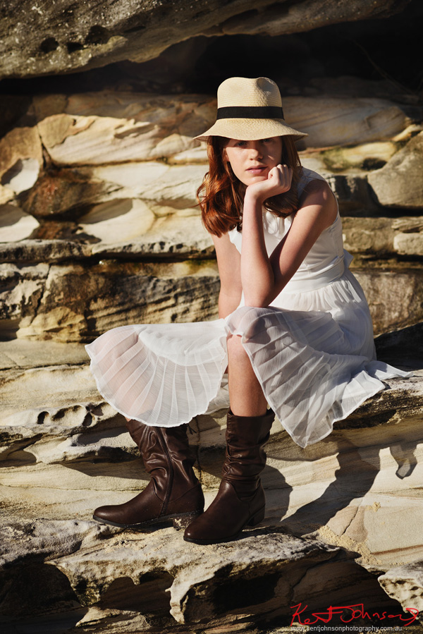 Teen modelling portfolio on location, seated pose, white dress, panama hat and boots. Photography by Kent Johnson