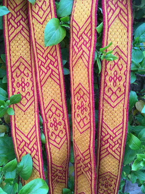 A photograph of several lengths of red and yellow tablet woven band, patterned with floral motifs and lattice work, against a leafy backdrop
