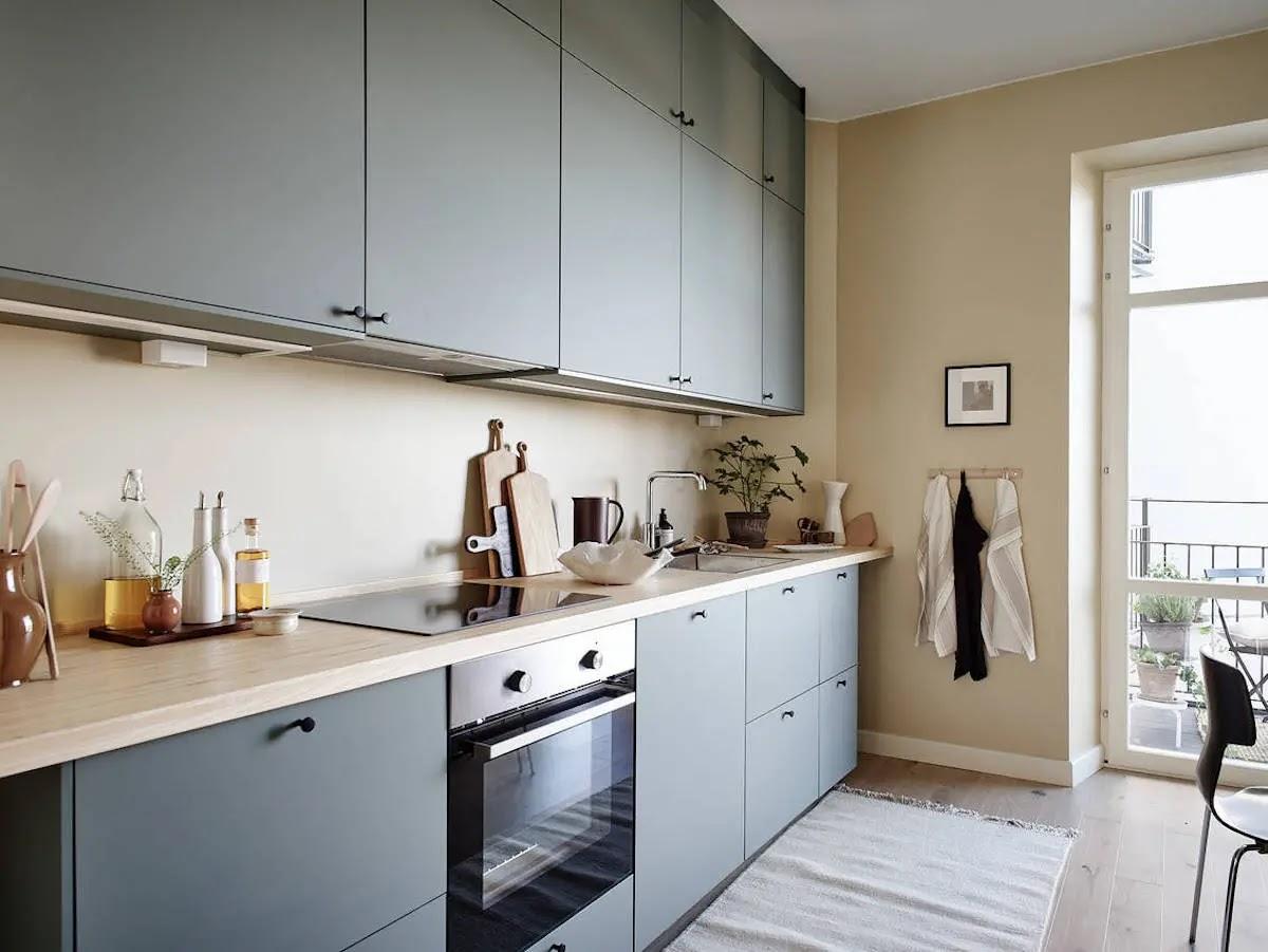 cocina con mobiliario de alto y bajo con encimera de madera y frentes en azul
