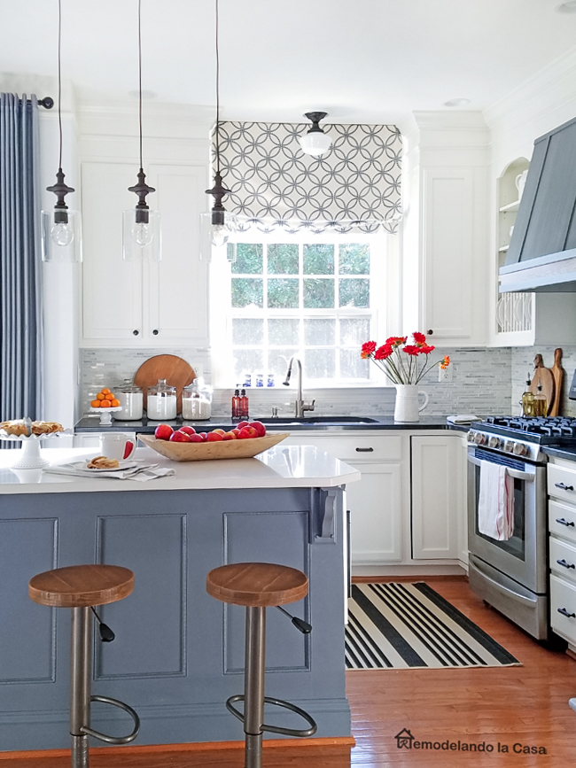 grey kitchen island and white cabinets with stripped rug and roman shade and red/orange accents