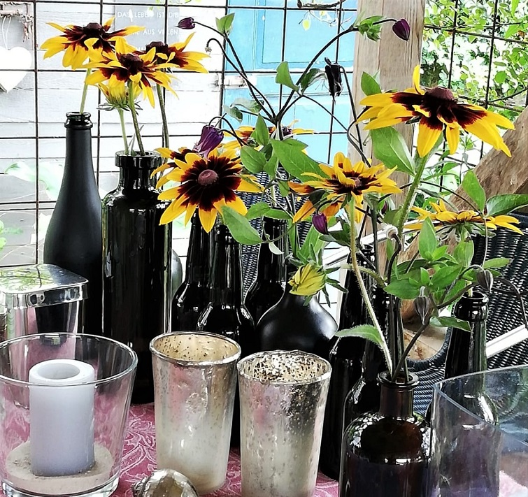 Gartendeko mit schwarzen Flaschen