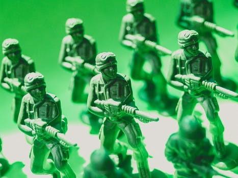 緑色の背景の中で戦闘態勢の軍隊の人形