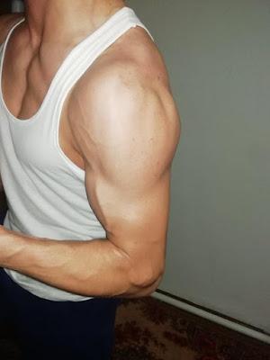 decak-pokazuje-misicave-bicepse-potkosulja-velike-oteknute-tricepse-ruke