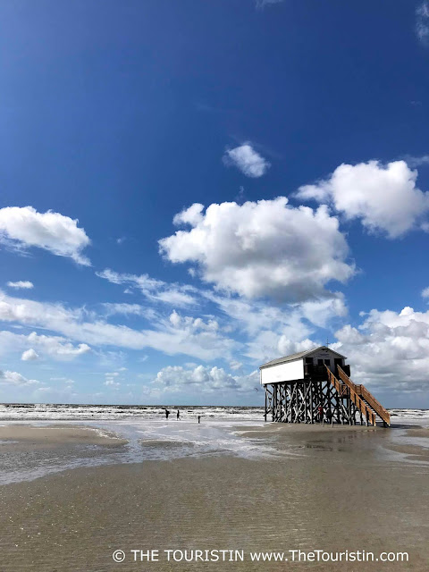 Three people at low tide next to a white wooden cottage on stilts in the sea under a bright blue sky dotted with clouds.