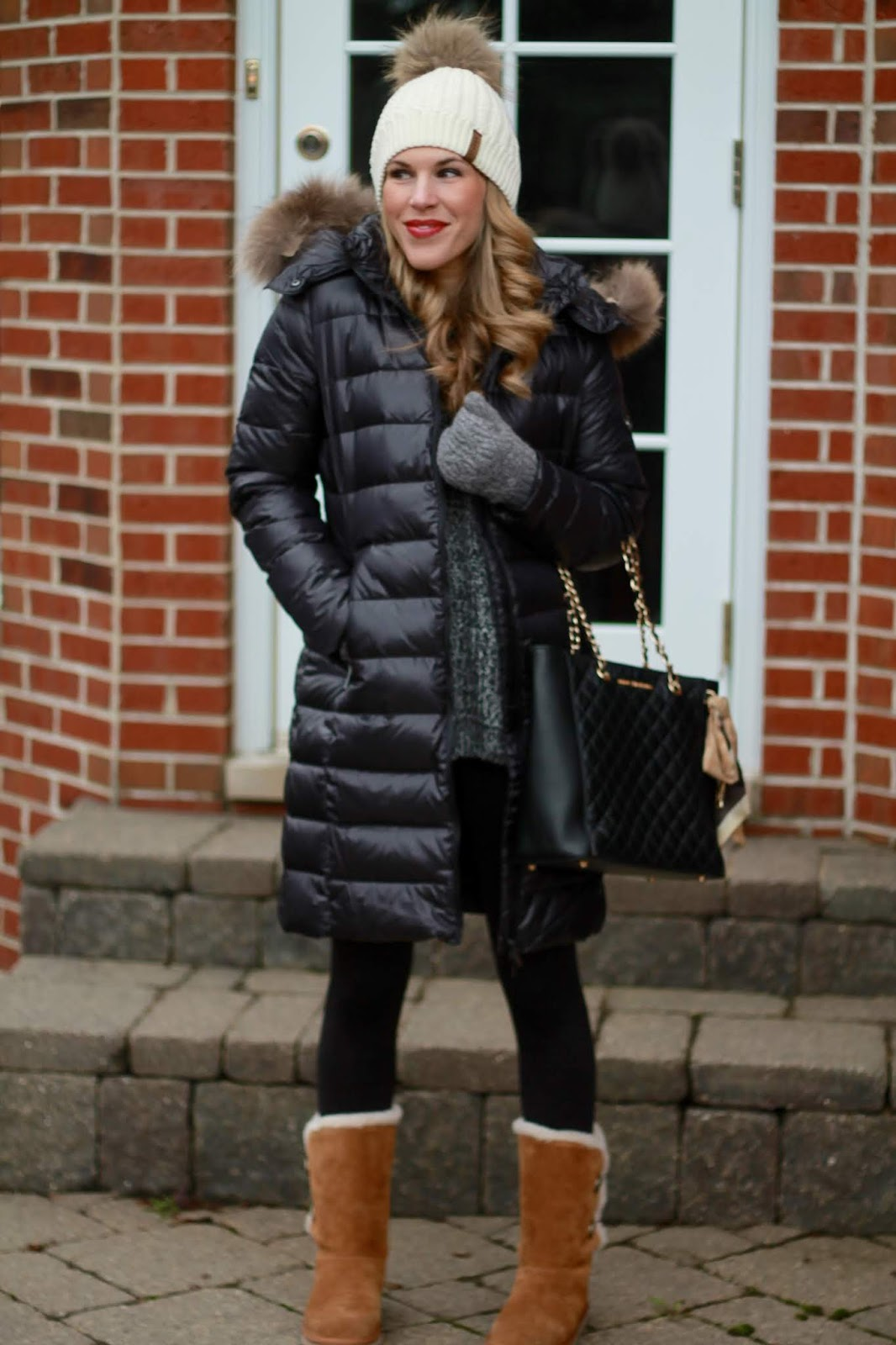 long black down coat, black marled tunic sweater, black leggings, greg michaels tote, koolaburra ugg boots, white fur pom hat