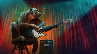 Affe auf Bühne mit Gitarre und Zigarette im Mund