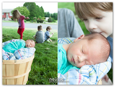 outdoor portrait of siblings on green grass while newborn baby sleeping soundly in basket outdoor portrait