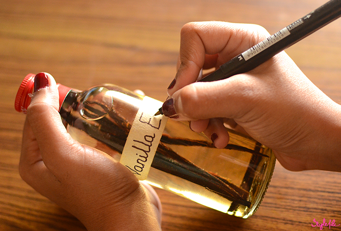 An image of a woman labelling a bottle of vanilla extract to make a do it yourself project of how to make vanilla extract at home