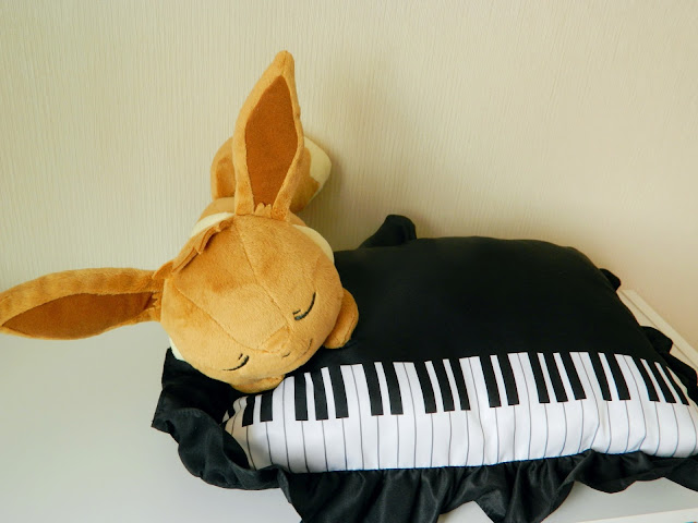A photo of a plush attached to a pillow, of the pokemon Eevee and a piano. Won playing Japanese game, ichiban kuji