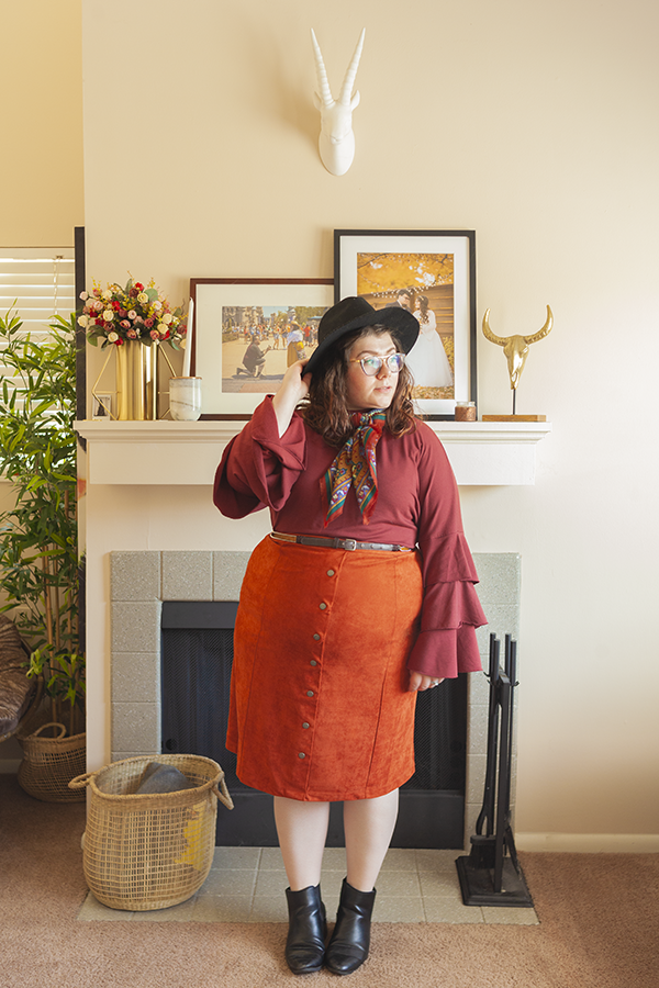 An outfit consisting of an oversized black floppy hat, a patterned warm tone neck scarf, a rust red long three tiered sleeve blouse tucked into a burnt orange button down midi skirt with black chelsea boots.