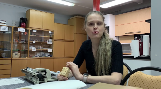 Linda sedí u pichtova Psacího stroje a v ruce drží B-kostku