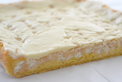 White Chocolate Marshmallow Cake Bars have a yellow cake base, a gooey marshmallow filling and white chocolate chips through out with a white chocolate frosting. Life-in-the-Lofthouse.com