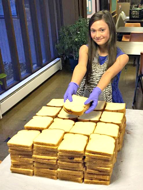 young girl volunteering and making peanut butter and jelly for the homeless