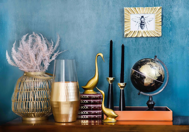 stock photo - cabinet with copper and gold accessories on top. Black and gold glove, gold vase