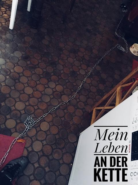 Lange Kette, die von dem Fußgelenk eines Sklaven zu einem Wandring führt. Text un Bild: Mein Leben an der Kette.