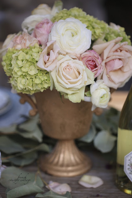 fresh flowers in gold container on table