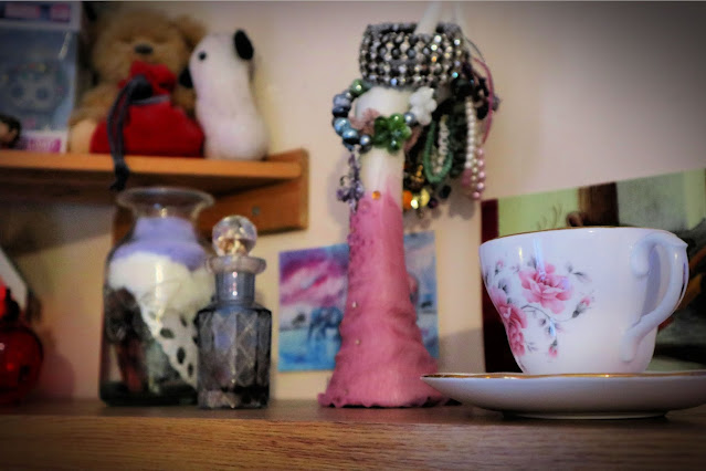 Two shelves, one in the background with stuffed animals and a Pop figure on and one with a china tea cup and saucer in the foreground and behind it a carafe, cut glass perfume bottle and jewellery hanger in the shape of a hand