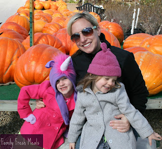 Woman sitting with 2 children, in front of pumpkins