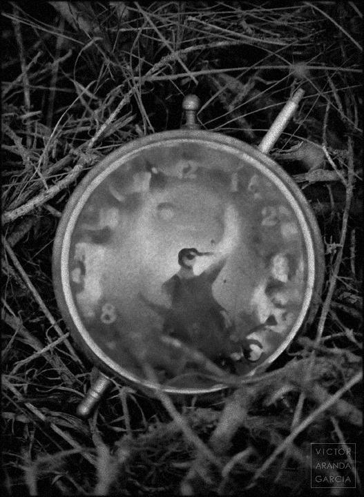 Fotografía de un reloj antiguo sobre un suelo silvestre con el perfil del fotógrafo reflejado en el cristal