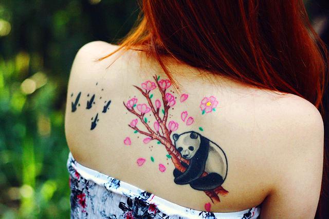 Espalda de una mujer siática, de pelo caoba, lleva n el homoplato el tatuaje de un oso panda aferrado a un cerezo