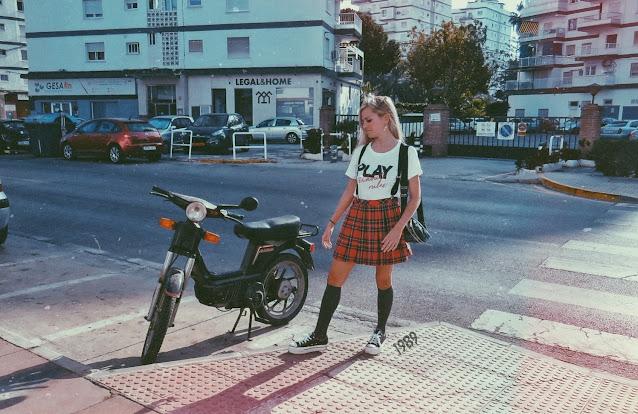 Alejandra Colomera vestida con camiseta blanca con mensaje, falda de tablas cuadros escoceses, tirantes, calcetas y zapatillas con Vespino