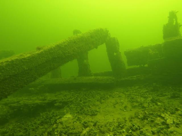 Vedenalainen kuva puisesta laivan hylystä vihertävässä vedessä.