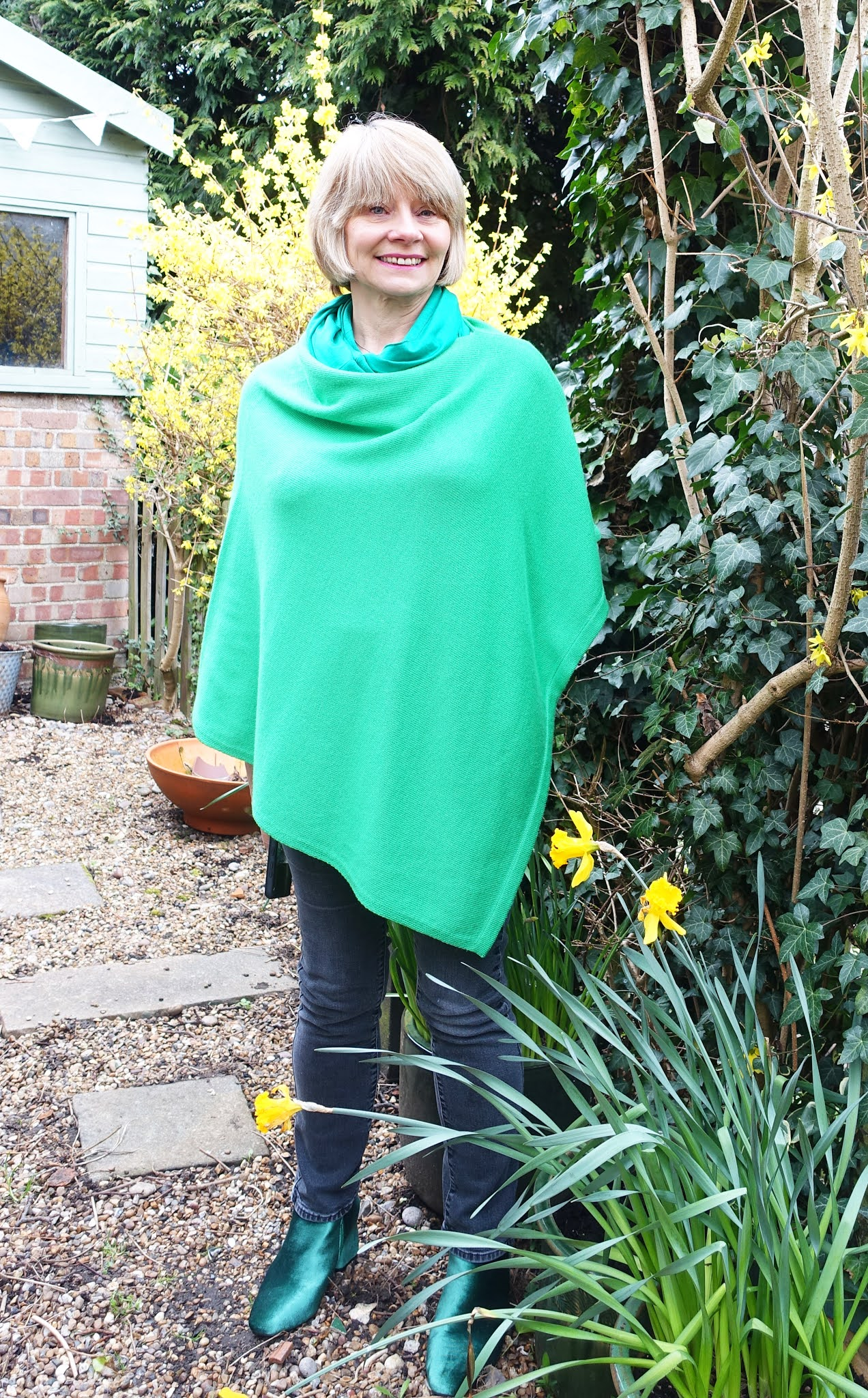 A bright green poncho for spring worn with jeans and statement green suede boots