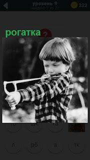 мальчик натянул резинку у рогатки и собирается стрелять