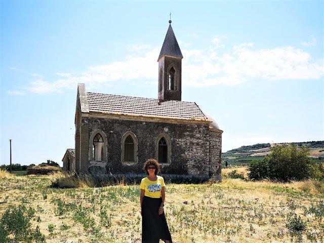 Donna con maglia gialla e chiesa abbandonata alle spalle