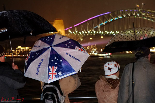 'Australia' umbrella in the rain, Sydney Harbour Bridge in the background at night - Vivid Sydney 2013 - Fujifilm X-Pro1, XF35mmF1.4 R.