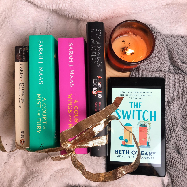 STack of books with their spines face up next to a kindle showing the cover of 'The Switch' by Beth O'Leary