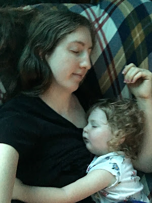 a woman takes a selfie while pretending to sleep with her baby, who is asleep on her arm