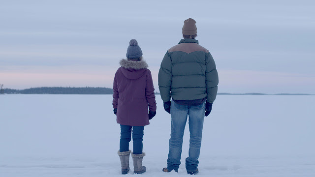a woman and a man stand in the snow in minnesota