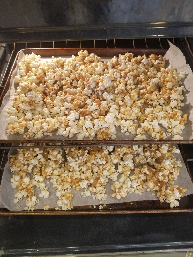 Two cookies sheets loaded with caramel coated popcorn and baking in the oven