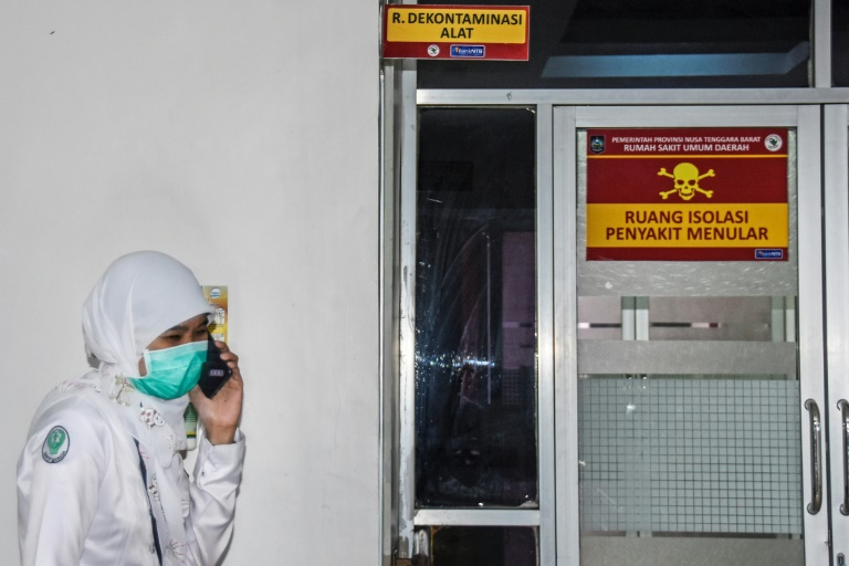 A health worker speaks by phone outside an isolation zone for patients with coronavirus symptoms in a public hospital in Mataram, Indonesia, on January 28, 2020.