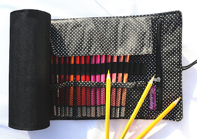 A black fabric roll, unrolled half way, to reveal a selection of watercolour pencils, with three yellow pencils resting on top.