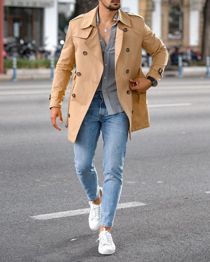 A man wearing a Long coat, jeans and a shirt combo outfit.