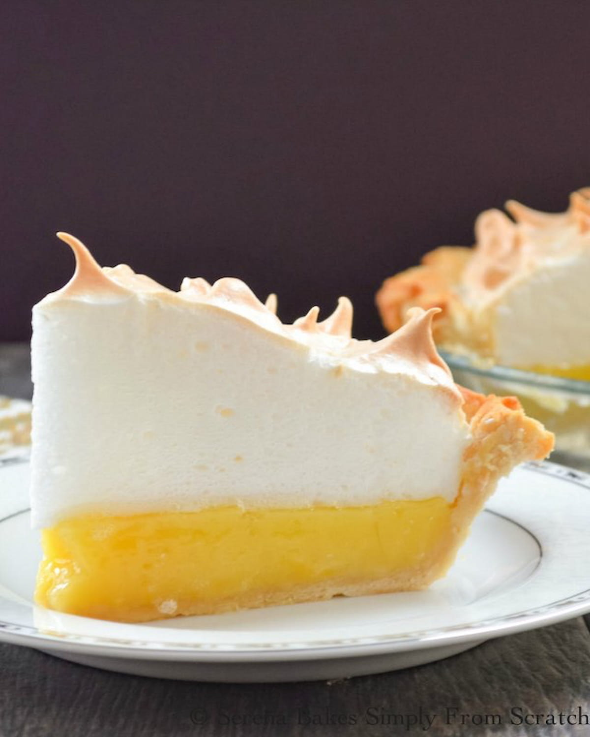 A slice of Lemon Meringue Pie topped with a weep free meringue on a white plate/
