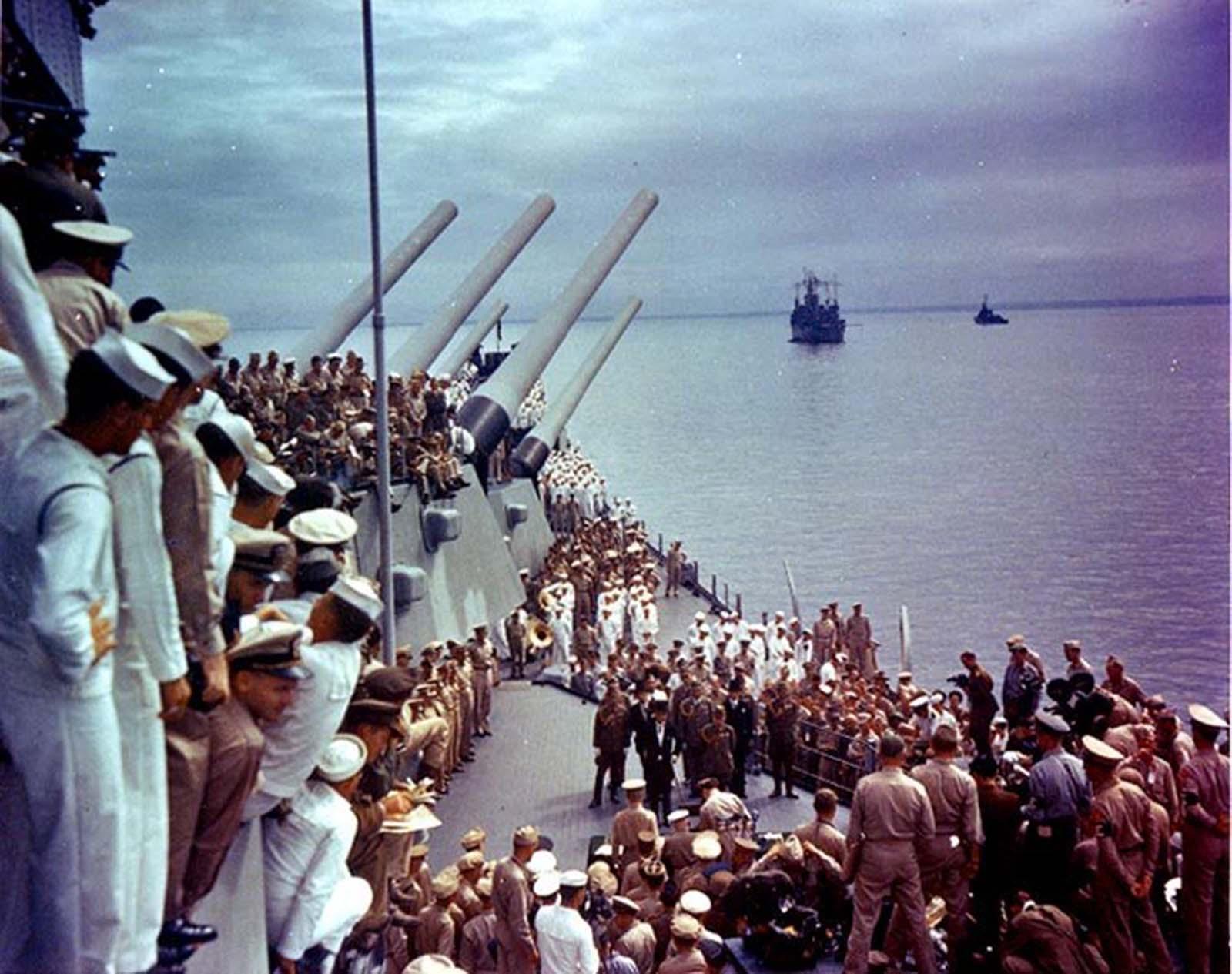 Amerikai katonák, akik figyelik a japán és az amerikai tisztviselőket, aláírják az előbbi átadási okmányát.  1945.