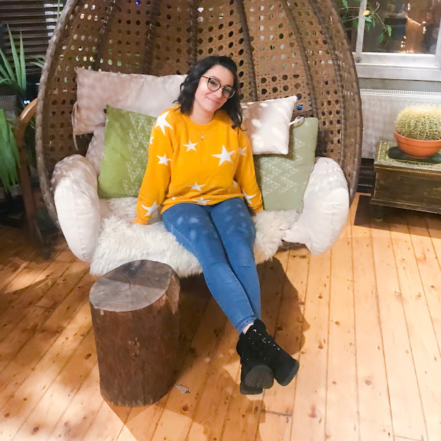 Me sitting in the wicker hanging chair smiling and wearing a bright yellow jumper with white stars on.