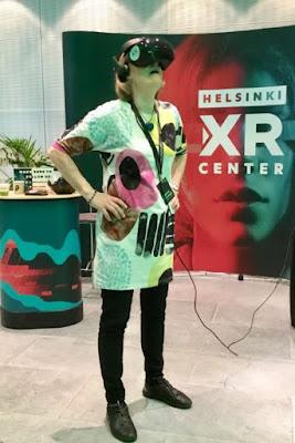 Matleena Laaksolla on päässä virtuaalilasit, Taustalla Helsinki XR Centerin seinäke