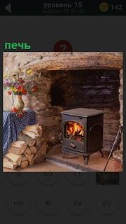 Небольшая печь в комнате горит и рядом сложены стопкой дрова