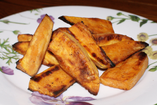 Side view of sweet potato wedges on a plate with purple flowers.