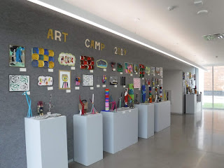 "smooth white pillars and a gray wall display brightly colored children's artwork and the words ""Art Camp 2019"""