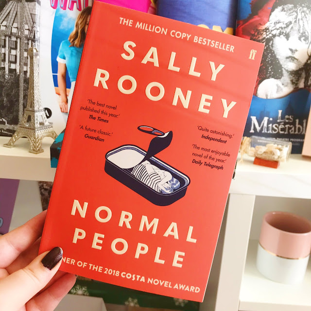 Normal People by Sally Rooney held up in front of musical programs on desk