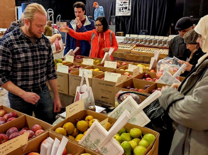 Customers selecting apples from cardboard boxes at indoor market