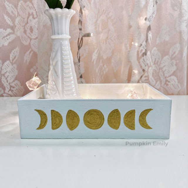 A wooden tray with painted moon phases on it.