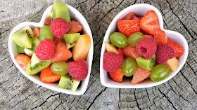 two heart shaped bowls full of fresh fruit salad