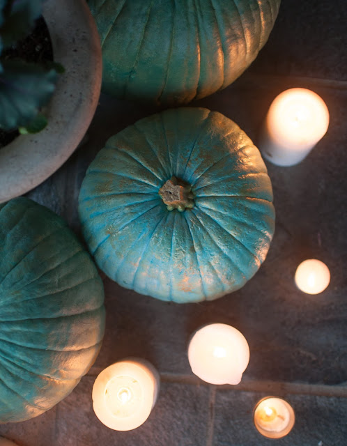 Blue Cinderella pumpkins and candlelight in a cozy vignette by Gwen Moss