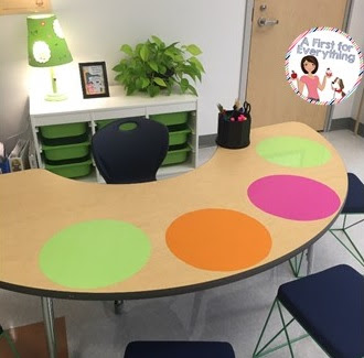 Guided reading table with Wall Pops helps to identify student space and they serve as dry erase boards when used with wipe-off markers. Bins behind the table hold materials needed for each guided reading group